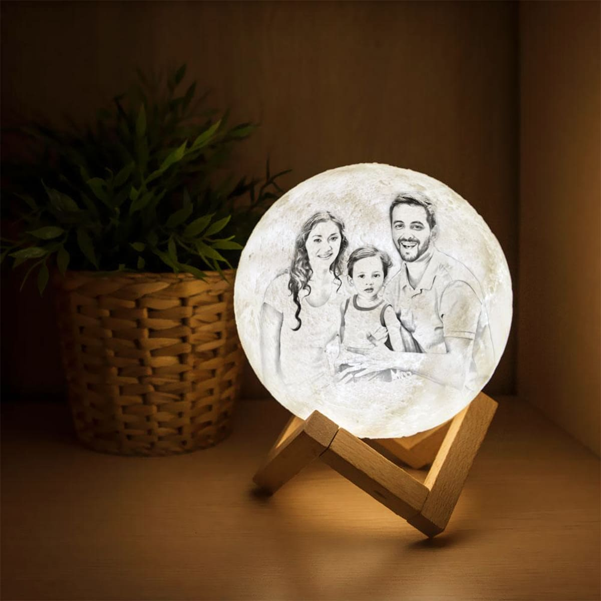 White color lamp with family painting on it placed on a wooden stand on a wooden table